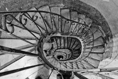 Old spiral stairs. Looking down an old winding spiral stairs with a metal rail Stock Photography