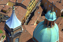 Old  spires Bologna Italy. Red tiles, old clock tower and Santi Bartolomeo e Gaetano church spires in the old city center seen from Asinelli Tower in Bologna Royalty Free Stock Photos