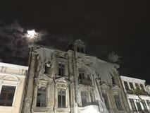 Old spooky ruin hotel and ful moon. Old hotel spooky in the night old architecture many windows stock photo