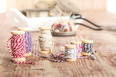 Old spools of thread, fabric, scissors on a wooden background Royalty Free Stock Photography