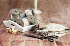 Old spools of thread, fabric, scissors on a wooden background Royalty Free Stock Photos