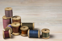 Old spools of thread on wooden background. Old spools of thread on a wooden background Royalty Free Stock Image