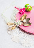 Old spoon with a ribbon on a pink plate with Easter egg Royalty Free Stock Image