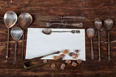Old spoons and brown sugar cubes with space for text. Old spoons and brown sugar cubes with place for text. Top view stock photos