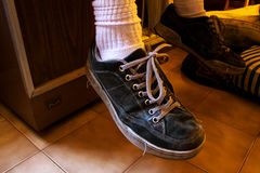 Old sport shoes. Ankles and feet wearing old sport shoes Stock Image