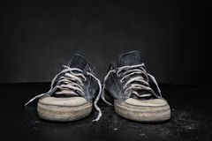 Old sports trainers. On grey stock photography