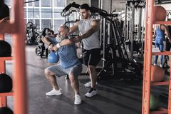 Senior concentrated man is having workout with his instructor. Old sportsman with beard is doing kettlebell goblet squats with young trainer which is standing stock photos