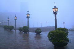 Old square on foggy night with street lights on Stock Photo