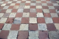 Old square tiles in a checkerboard pattern lying. On the area of Montenegro in Kotor Stock Photography