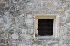 Old square window with bars in a stone wall Stock Photos