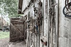 Old stables, on the wall hanging various tools and horse harness, at an angle Royalty Free Stock Photography