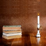 Old stack of books with candlestick  and burning candle Royalty Free Stock Images