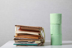 Old stack of waste paper and a roll of toilet paper Stock Photo