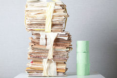 Old stack of waste paper and a roll of toilet paper Stock Images