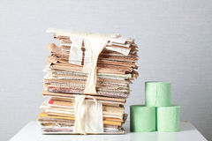 Old stack of waste paper and a roll of toilet paper Royalty Free Stock Photos