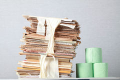 Old stack of waste paper and a roll of toilet paper Royalty Free Stock Images