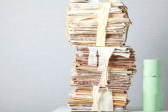 Old stack of waste paper and a roll of toilet paper Stock Photography