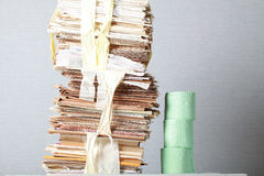 Old stack of waste paper and a roll of toilet paper Royalty Free Stock Photo