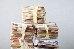 Old stack of waste paper and a roll of toilet paper Royalty Free Stock Image
