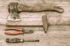 Old stained axe, hammer, pliers and screwdriver on old wooden su Stock Images