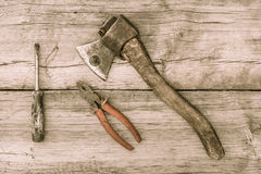Old stained axe, pliers and screwdriver on old wooden surface Royalty Free Stock Image