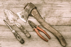 Old stained axe, pliers, trowel and screwdriver on old wooden su Royalty Free Stock Photo