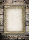 Old stained paper sheet in picture frame on wooden background Royalty Free Stock Photography