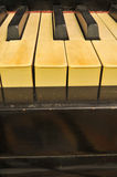 Old stained piano keys. A shot of an old piano with stained ivory keys with missing ivory pieces missing that was not maintained very well Stock Photography
