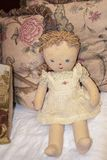 Old stained rag doll with painted eyes and mouth and embroidered searsucker pinafore propped against floral fringed pillows - royalty free stock images