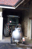 Old Stainless Ball Milk Tank and Tractor. An image of a traditional old european stainless sphere milk tank on tow by a tractor parked in an old Swiss barn royalty free stock photos
