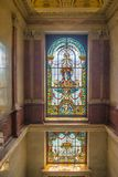 Old staircase in a palace of a factory owner. Beautiful vintage marble staircase in eclectic historic style with stained glass art window belonging to a former Royalty Free Stock Photo