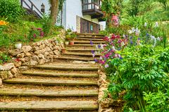 Old stairs footpath lined with flowers and rocks leading to house on a hill stock photography