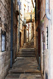 Old stairs on narrow pathway stone buildings. Dark old stairs on narrow pathway with stone buildings in Dubrovnik, Croatia Royalty Free Stock Photos