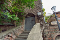 Old stairs to brick house with street lamps in historical city Stock Images