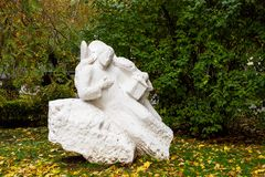 Old statue of angel in autumn forest. Old dirty statue of an angel in an autumn forest Royalty Free Stock Images