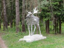 Old statue of an Elk with antlers in the woods. stock photos