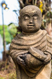 Old statue of a little monk standing and holding monk's alms-bowl Royalty Free Stock Photography