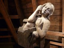 Old statue made of stone. Old statue archived under the wooden roof of the historic building Stock Image