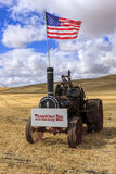 Old steam engine with US flag. The US flag on an old steam engine, in a wheat field at the Colfax Threshing Bee in Colfax, Washington stock image