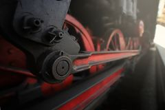 An old steam engine from which chassis, coupling rod and control are visible stands on the platform in bright light. Wide angle view on the chassis, coupling royalty free stock photo