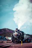 Old steam locomotive against blue cloudy sky, vintage train Stock Image