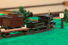 The old steam locomotive carries the freight train. Toy railroad. Carefree childhood Stock Image