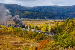 Old steam locomotive in the Circum-Baikal Railway with smoke in autumn. Old steam locomotive in the Circum-Baikal Railway with smoke in cloudy wearther autumn Royalty Free Stock Photos