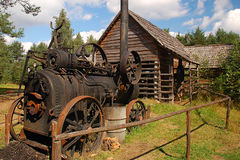 Old steam machine staying in a backyard. In the back old cottage Royalty Free Stock Images