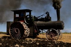 An old coal burning steam powered tractor. An old steam powered tractor using coal blows black smoke over the environment as it plows a the stubble of a wheat stock photography