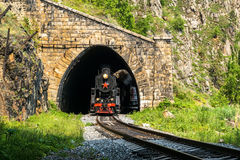 Old steam train leaves the tunnel on Circum-Baikal Railway Stock Image