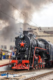Old steam train is leaving a station. Vintage Steam engine locomotive train moving down railroad track towards camera Royalty Free Stock Image