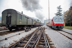 Old steam train and new electric train. Old steam train is living the station, new electric train coming into the station Royalty Free Stock Photos