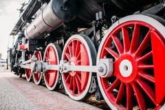 Old steam train, red wheels closeup. Vintage locomotive. Railway engine, ancient railroad vehicle Royalty Free Stock Image