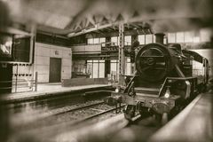 Old steam train, vintage locomotive entering train station - retro photography stock photography